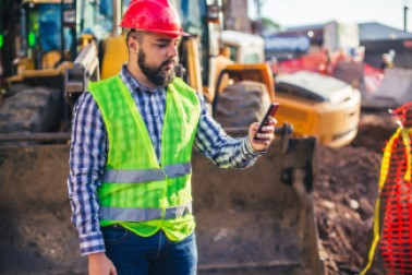 Construction worker checks cell phone